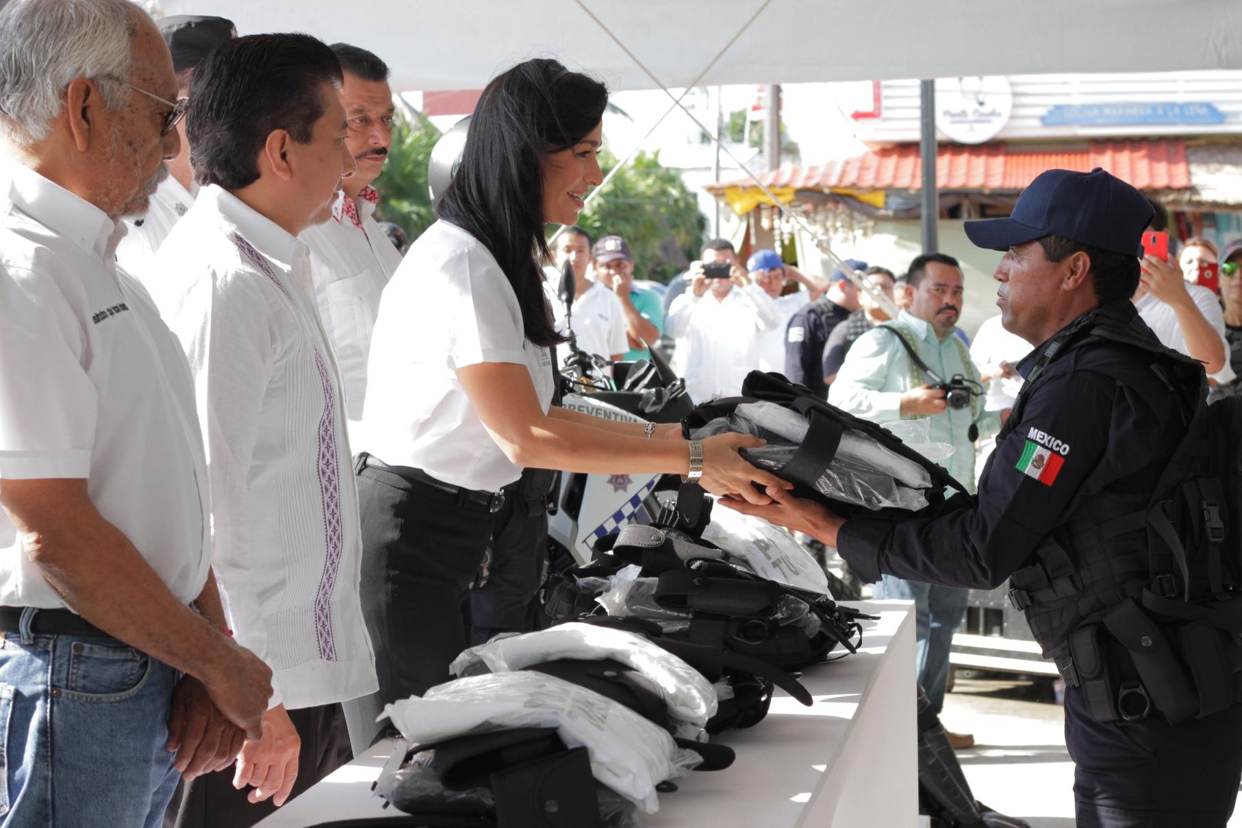 Laura Fernández entrega uno de los 200 uniformes a un agente